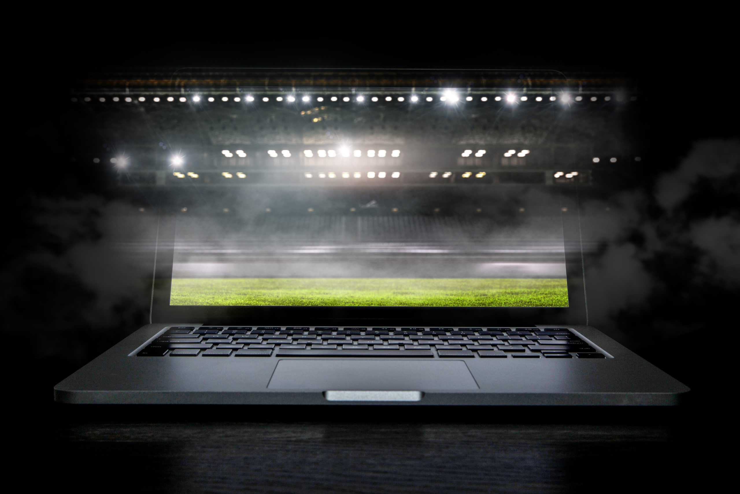 Sport arena with green field and spotlights on laptop screen. Mixed media