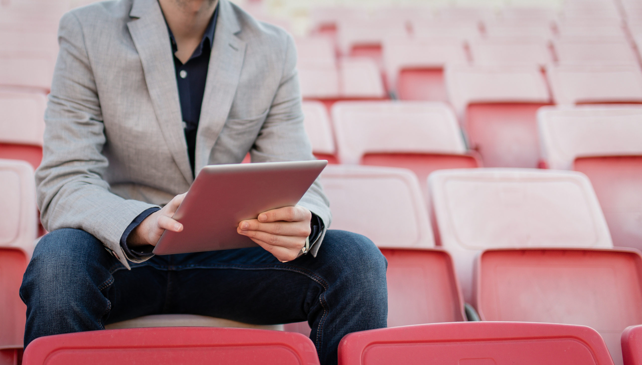 Young and successful football manager working on a tablet, and sitting on the stands alone.